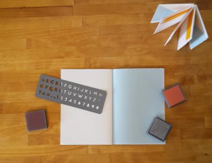 carnet, encres et pochoir lettre